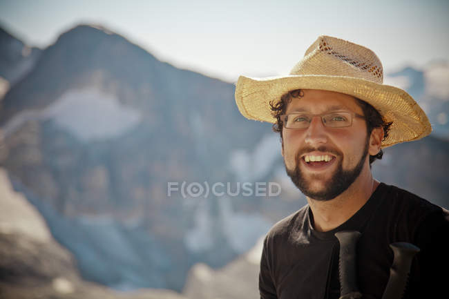 Portrait of a bearded hiker wearing a straw hat and glasses. — Stock Photo