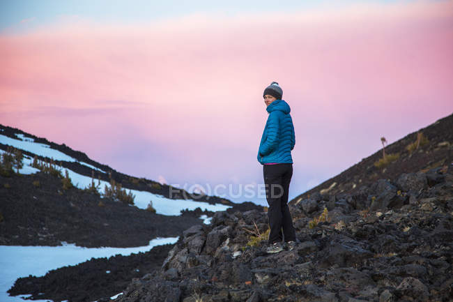 Woman in warm clothing standing against mountains at sunset — Stock Photo