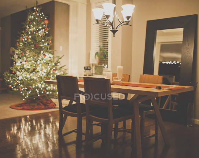Árbol de Navidad y la mesa servida en el comedor de casa residencial - foto de stock