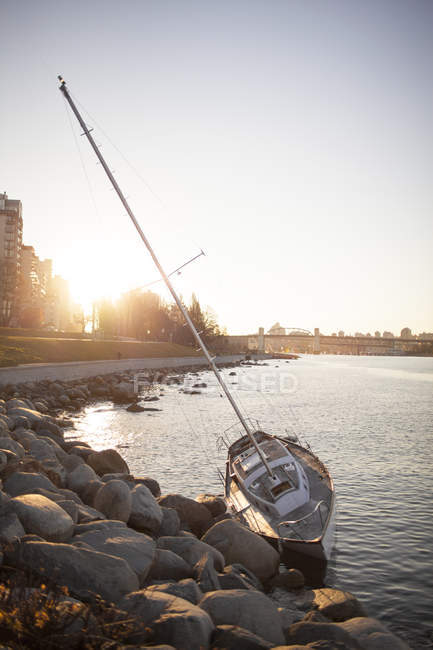 Small sailboat smashed up on the rocky shoreline of Sunset Beach, Vancouver — Stock Photo