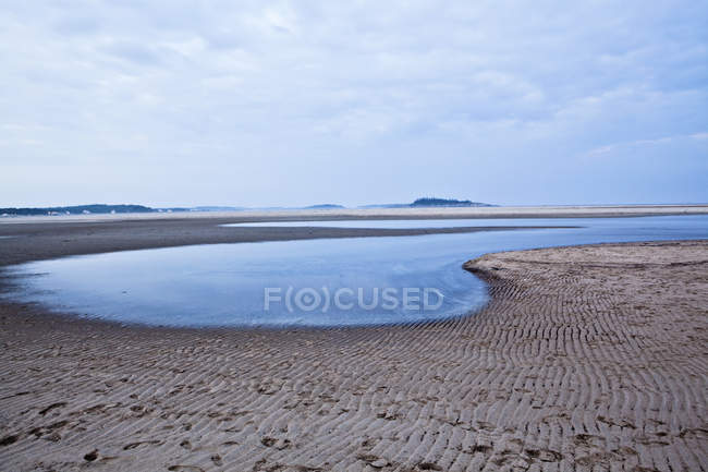 The tide slowly creeps up the shoreline of Popham Beach, Maine. — Stock Photo