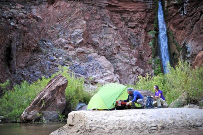 Gli escursionisti di installazione camp su una spiaggia lungo il fiume Colorado vicino plumeting 180 piedi Deer Creek Falls nel Grand Canyon di fuori di Fredonia, Arizona novembre 2011. Il ciclo di 21,4-mile inizia presso il sentiero di Bill Hall sul North Rim e scende 200 — Foto stock