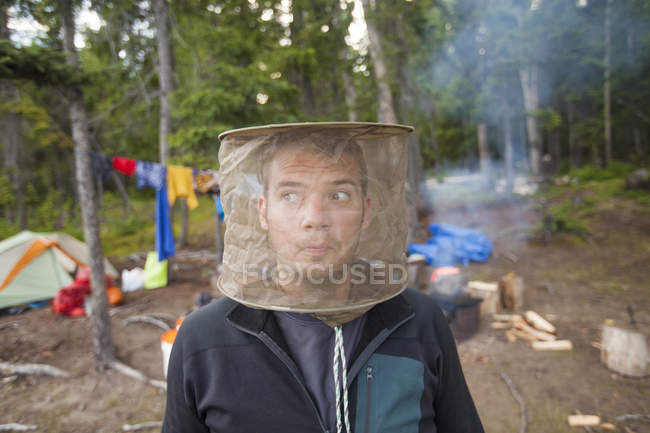 A man poses with a mosquito head net on with his camp behind him. — Stock Photo
