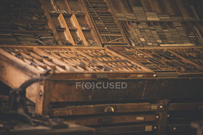 Antique wooden printing press boxes filled with metal plates used in historical printing — Stock Photo