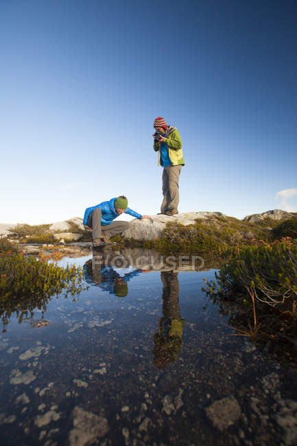 A young woman explores the microclimate of an alpine lake while her partner captures a photo of her. — стокове фото