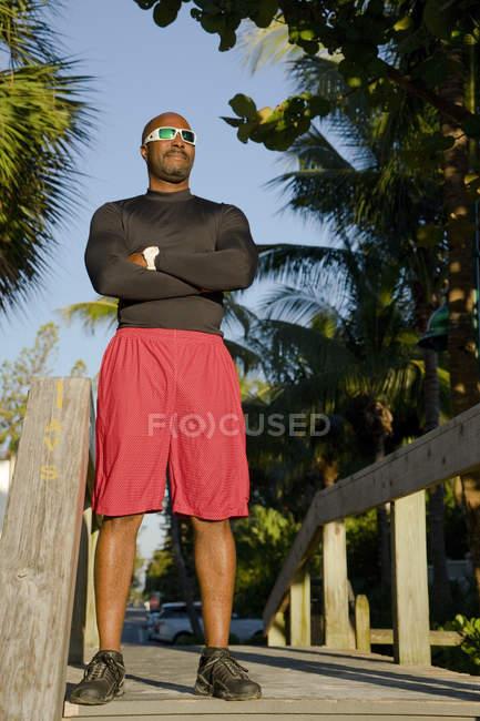 Спортивная(ый) человек с руками, скрещенными на пляж дощатый, тропической обстановке — стоковое фото