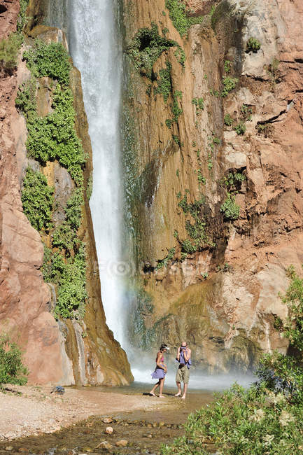 Hikers swim in the pool below 180-foot Deer Creek Falls in the Grand Canyon outside of Fredonia, Arizona November 2011.  The 21.4-mile loop starts at the Bill Hall trailhead on the North Rim and descends 2000-feet in 2.5-miles through Coconino Sandst — Stock Photo
