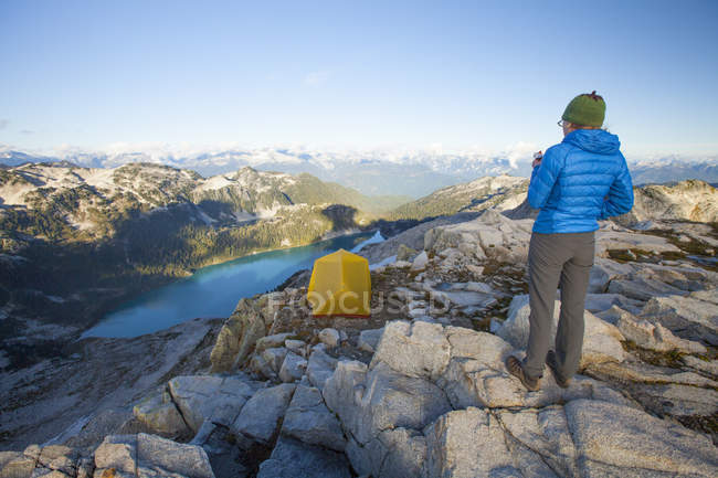 A young female backpacker eats an energy bar for dinner while looking down towards Pinecone Lake from Seed Peak in Pinecone Burke Provincial Park, British Columbia, Canada. — Stock Photo