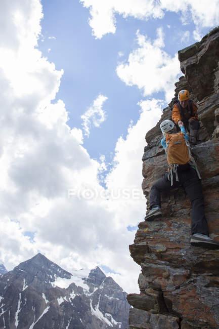 Bergführer unterstützt Frau Kletterer, Felswand über Bergen — Stockfoto
