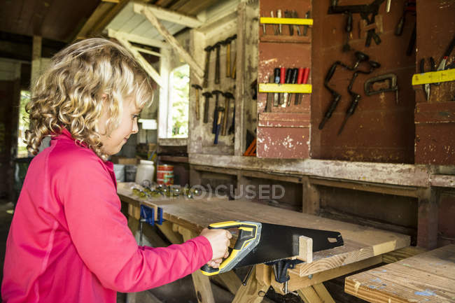 Young Girl Cutting Plank With Saw At Workshop — стоковое фото