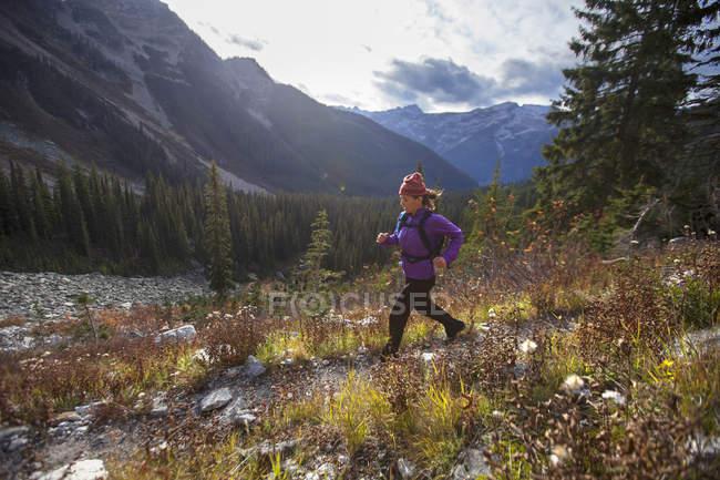 Vista laterale della donna che corre sul sentiero in montagna — Foto stock