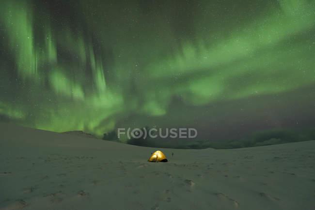 Кемпинг в снегу покрыты пейзаж с Северное сияние в ночное время — стоковое фото
