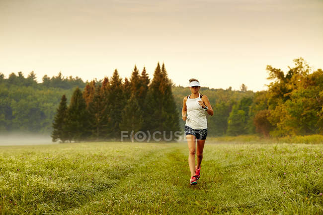 Female Runner Running On Grassy Landscape During A Foggy Morning — Stock Photo