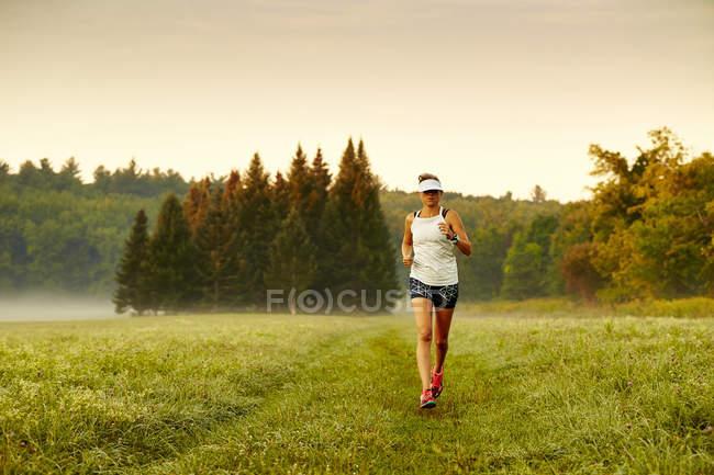 Corridore femminile in esecuzione sul paesaggio erboso durante una mattina nebbiosa — Foto stock