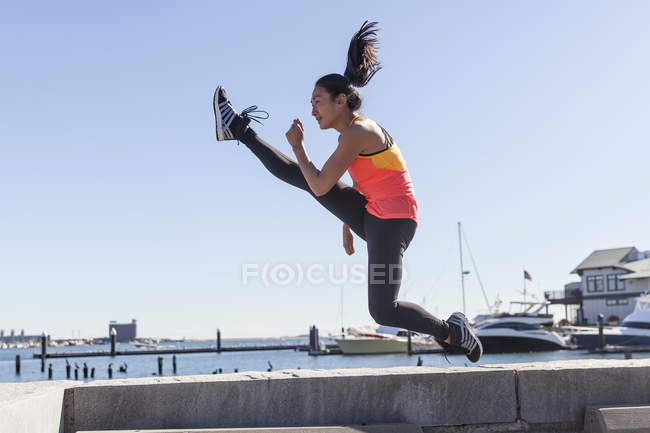 Photograph of fit woman performing jumping kick — Stock Photo
