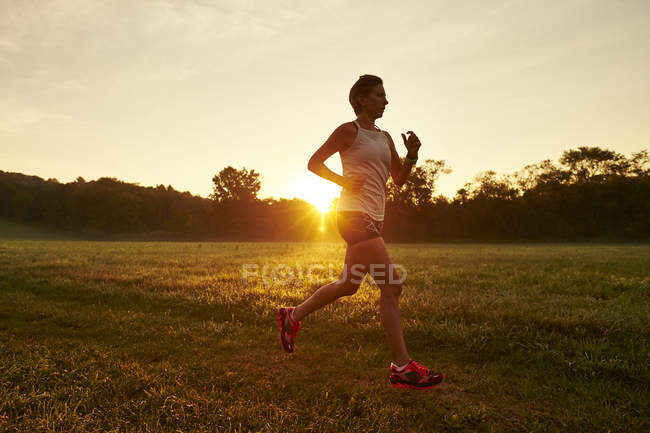 Woman Running On Grassy Field During Sunrise — Stock Photo