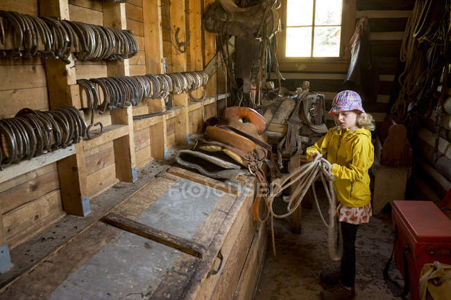 Young girl coiling rope for horseback riding — Photo de stock
