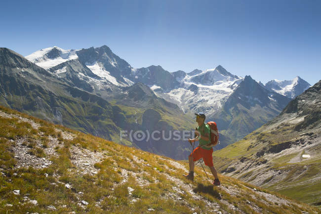 Hiker walking up on hill with mountains on background — Stock Photo
