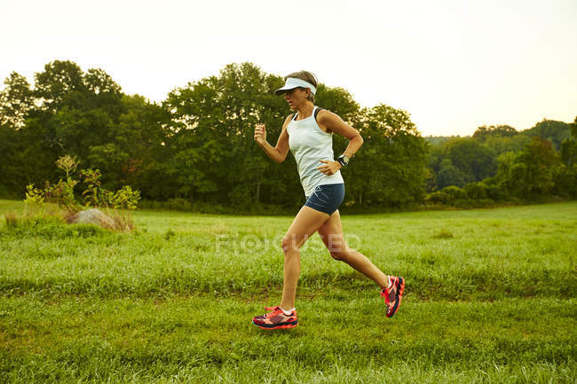 Female Runner Running Through A Field On A Foggy Morning — Stock Photo