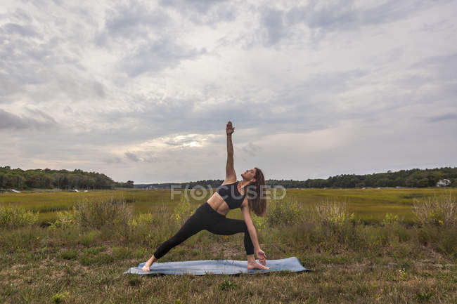 Beautiful Young Woman In A Twist Stretching Towards The Sky Doing Yoga At Sunset — Stock Photo