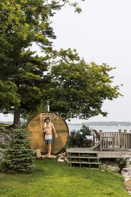 Homme restant à côté du sauna d'arrière-cour à côté de la rivière — Photo de stock
