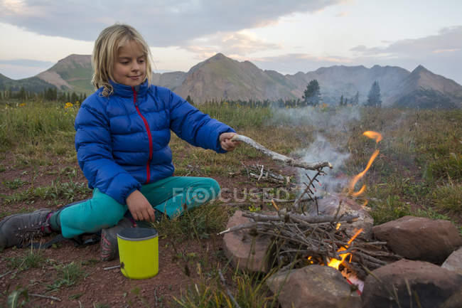 Young girl sitting by campfire against mountains - foto de stock