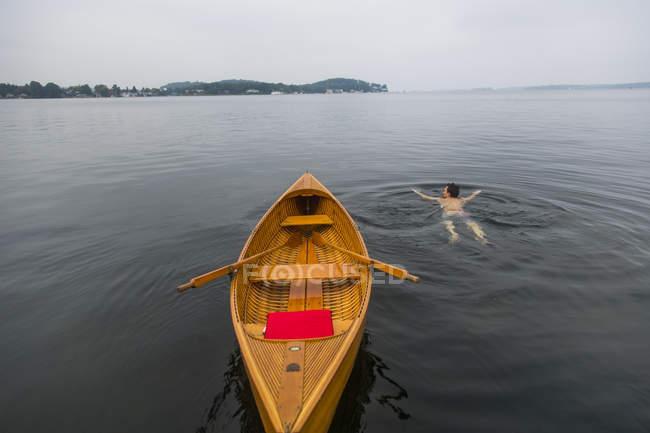 Homme nageant à côté du bateau en bois de ligne — Photo de stock