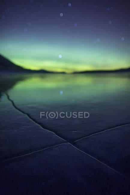 Aurora über Eis gefroren Risse In Abraham Lake — Stockfoto