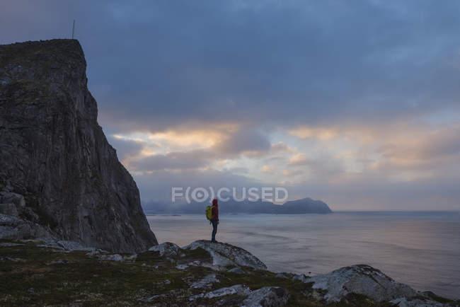 Alpinista feminina em pé abaixo Mntind, Flakstady, Ilhas Lofoten, Noruega — Fotografia de Stock
