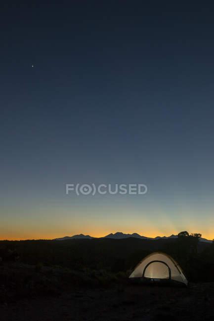 Beleuchteten Zelt unter die La Sal Mountains während des Sonnenuntergangs im Paradox-Tal, Naturita, Colorado — Stockfoto