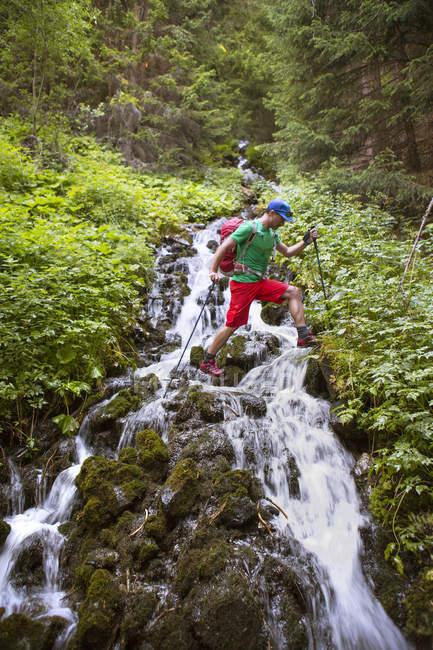 Maschio escursionista che scavalca il torrente di montagna — Foto stock