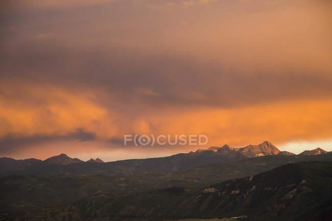 Mountain scene with beautiful cloudy sunset — Stock Photo