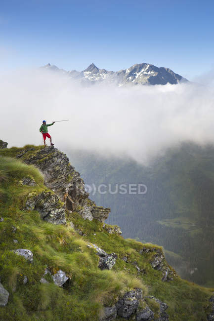 Hike on steep ridge pointing with hiking pole with mountain range in background — Stock Photo