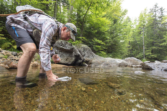 A Fly Fisherman Gathering A Sample Of Freshwater To Test For The Presence Of Microplastics — Stock Photo