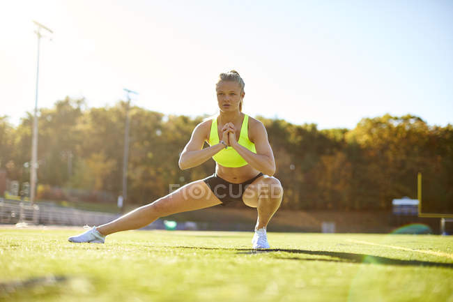 A Female Athlete Doing Stretching On The Field — Stock Photo