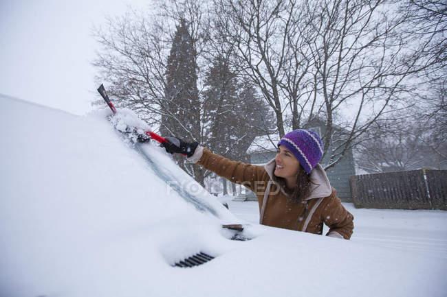 Frau räumt Windschutzscheibe nach Schneefall ab — Stockfoto