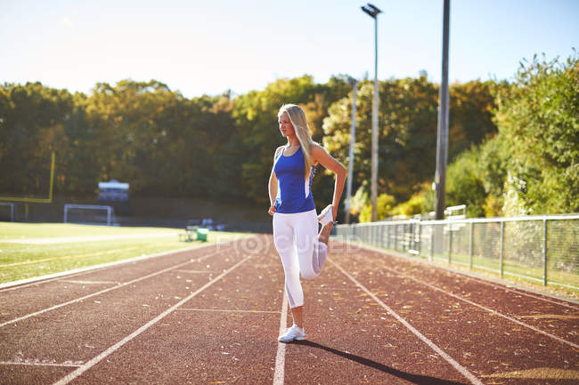 A Female Runner Doing Stretching On The Track — Stock Photo