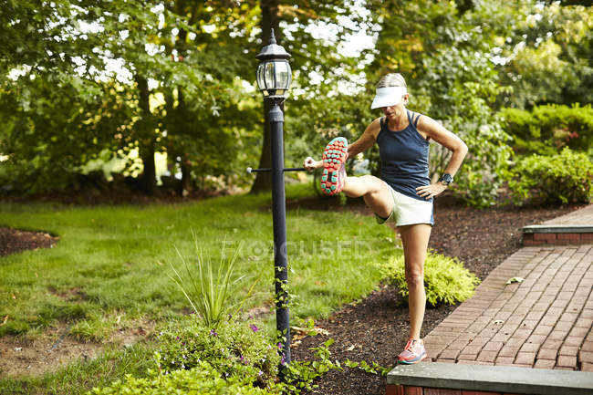A Female Runner Stretches Before Her Run On A Lawn — Stock Photo