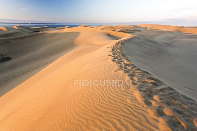 Песчаные дюны Маспаломас во время восхода с морем на фоне — стоковое фото