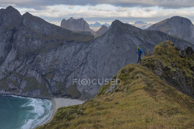 Female hiker walking along narrow ridge near Storskiva mountain peak, Moskenesy, Lofoten Islands, Norway — Stock Photo