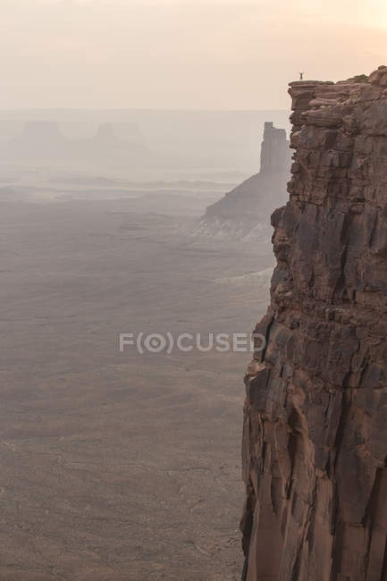 Hiker standing at sharp cliff edge at Green River Overlook in Canyonlands National Park, Utah. — Stock Photo
