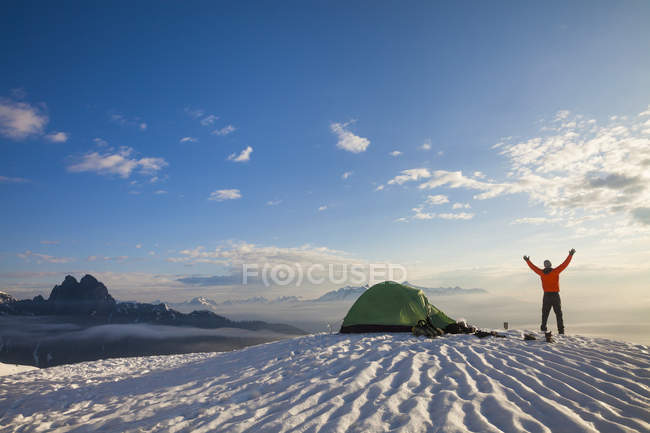 A Camper Lifting His Hand As He Watches The Sunrise From His Campsite On A Snow Covered Mountain — Stock Photo