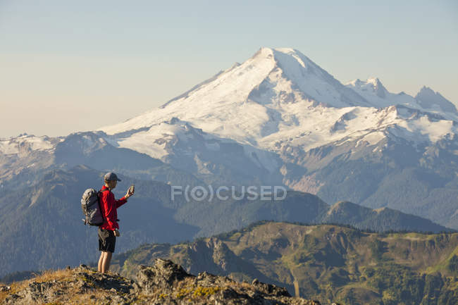 A Backpacker Checks His Phone While Hiking In North Cascades National Park — Stock Photo