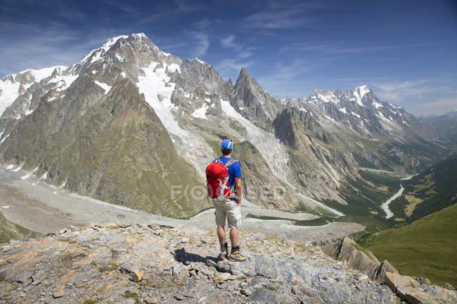 Hombre caminante sobre Val Veny, cerca de Courmayeur con el Mont Blanc, dominando la línea del cielo - foto de stock