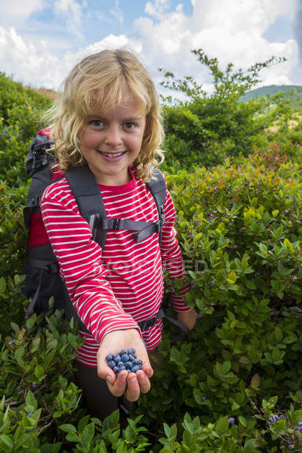 Young Girl Holding Blueberries And Smiling At Camera — Photo de stock