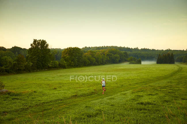 A Woman Running Through A Field On A Foggy Morning — Stock Photo