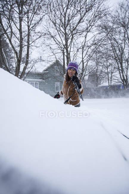 Frau räumt Fahrzeug nach Schneefall — Stockfoto