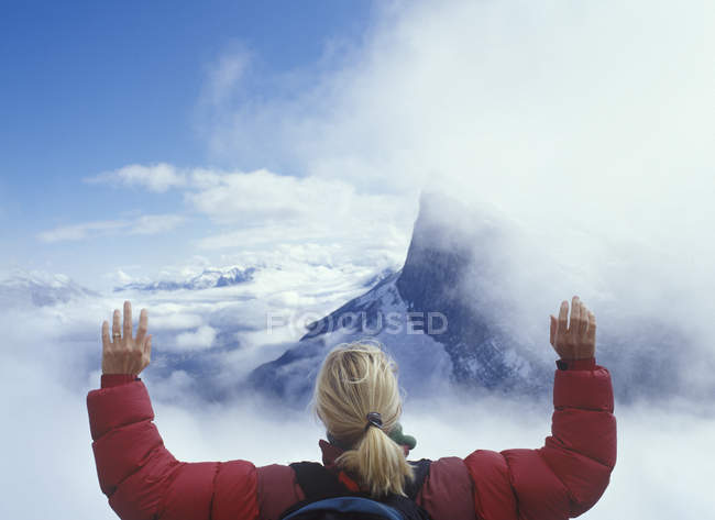 Head and shoulders of woman in clouds above mountains — Stock Photo