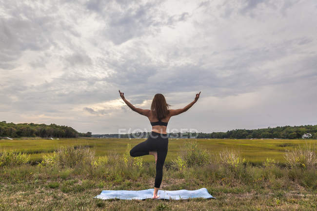Beautiful Young Woman In Tree Pose Doing Yoga At Sunset — Stock Photo