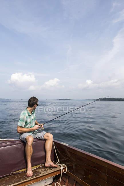 Pêche de mouche d'homme sur le bord du bateau en bois — Photo de stock
